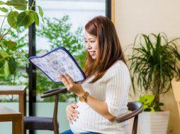ケースに入った母子健康手帳を手に笑顔の妊婦さん