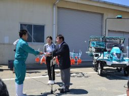 目録を受取る県立農業大学校学生代表の村田さん(左) 贈呈された多目的田植え機(右)
