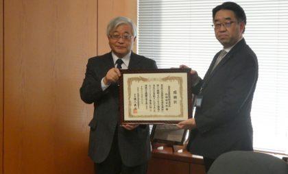 公益社団法人 北海道交通安全推進委員会 吉野三郎筆頭副会長(左)からJA共済連北海道 佐藤久副本部長(右)へ感謝状が贈られました